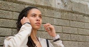 Vooraanzicht van jonge Afrikaanse Amerikaanse vrouw die oortelefoons in de stad 4k dragen stock videobeelden