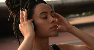 Vooraanzicht van jonge Afrikaanse Amerikaanse vrouw het luisteren muziek op hoofdtelefoons in de stad 4k stock footage