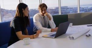 Vooraanzicht van jonge Kaukasische bureaustafmedewerkers die aan laptop bij lijst in modern bureau 4k werken stock footage