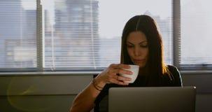 Vooraanzicht van jonge Kaukasische onderneemster het drinken koffie terwijl het werken aan laptop in bureau 4k stock video