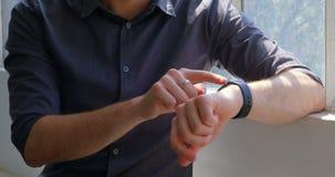 Vooraanzicht van jonge zakenman gebruikend smartwatch en zittend dichtbij venster van modern bureau 4k stock footage
