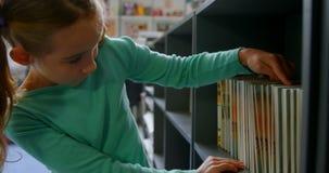 Vooraanzicht van Kaukasisch schoolmeisje die boeken op boekenplank zoeken in bibliotheek op school 4k stock footage