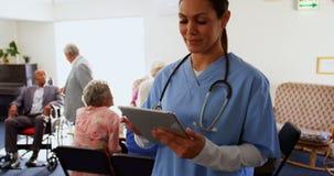Vooraanzicht van Kaukasische vrouwelijke arts die digitale tablet gebruiken bij verpleeghuis 4k stock video