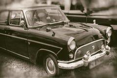 Vooraanzicht van klassieke uitstekende zwarte die auto op gras wordt geparkeerd - retro fotografie royalty-vrije stock fotografie