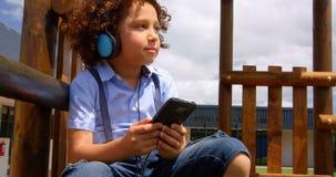Vooraanzicht van mengen-rasschoolmeisje het luisteren muziek op mobiele telefoon in de schoolspeelplaats 4k stock videobeelden