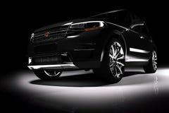Vooraanzicht van moderne zwarte SUV-auto in een schijnwerper Royalty-vrije Stock Afbeeldingen