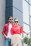 vooraanzicht van modieus jong paar van modellen in zonnebril status royalty-vrije stock afbeeldingen