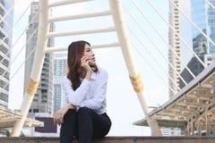 Vooraanzicht van mooie jonge Aziatische vrouw zitting en het spreken op telefoon bij stedelijke stadsachtergrond Stock Foto