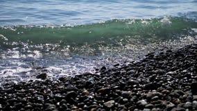 Vooraanzicht van overzeese golven die op kiezelstenen breken stock footage