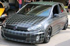 Vooraanzicht van plaid geschilderd Volkswagen Golf GTI Royalty-vrije Stock Afbeelding