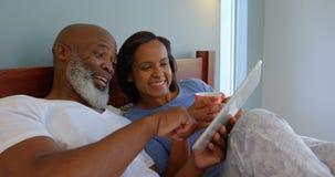 Vooraanzicht van rijp Kaukasisch paar die digitale tablet op bed in een comfortabel huis 4k gebruiken stock footage