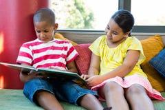 Vooraanzicht van siblings die boek thuis lezen Royalty-vrije Stock Foto