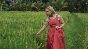 Vooraanzicht van slow-moving geschoten een jong meisje die een rode kleding met een lange rok en groene grote oorringen, losse la stock video