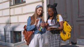 Vooraanzicht van twee mooie studenten die van Afrikaanse en Europese afdaling, zich verenigen De vrouwen bestuderen samen in a stock videobeelden