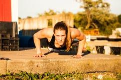 Vooraanzicht van vrouw die opdrukoefeningen buiten doen Royalty-vrije Stock Foto