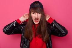 Vooraanzichtportret van boos meisje met lang haar en make-up in het toevallige jasje die van het stijl zwarte leer en zich in stu stock foto