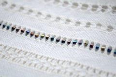 Voorbeeld van het borduurwerkpatroon met kralenversiering op witte stof stock afbeeldingen
