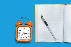 Voorbeeldenboek, wekker en een pen stock afbeelding