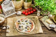 Voorbereide pizza met verse ingrediënten klaar aan het koken Stock Fotografie
