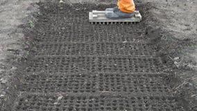 Voorbereidend de grond voor het planten van zaden Gebruikend tellershulpmiddel om celgaten te maken stock videobeelden