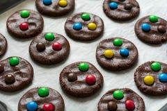 Voorbereidend eigengemaakte die chocoladekoekjes met gekleurde suikergoeddalingen worden verfraaid Stock Fotografie