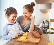 Voorbereiding van de moeder van het familieontbijt en de kok van de kinddochter stock afbeelding