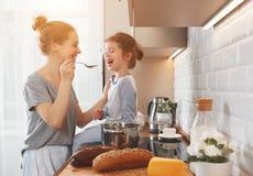Voorbereiding van de moeder van het familieontbijt en de kok van de kinddochter stock afbeeldingen