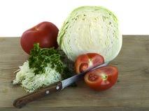 Voorbereiding van koolsalade met tomaat en kruiden Stock Foto's