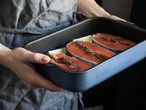 Voorbereiding van zalm Vrouwelijke handen met een kalkplak Een pot met ruwe zalmlapjes vlees royalty-vrije stock afbeelding