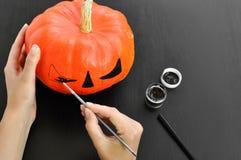Voorbereiding voor Halloween: de verf oranje pompoen van vrouwen` s handen met zwarte verf Closup Het concept van de vakantiedeco royalty-vrije stock foto's