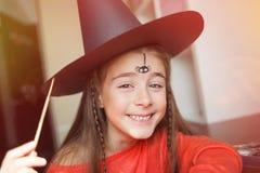 Voorbereiding voor Halloween kind in een heksenuitrusting die gezicht het schilderen doen Leuke Spin diy idee van eenvoudig kostu stock foto's