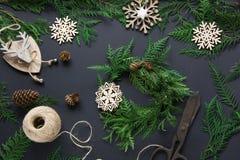 Voorbereiding voor Kerstmisvakantie Kerstmisworkshop van kroon, decor, streng, takjes en sneeuwvlokken De vrouw bereidt een kroon royalty-vrije stock afbeelding
