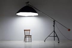 Voorbereiding voor studio die schieten: lege stoel en studioverlichting Stock Afbeeldingen