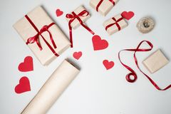 Voorbereiding voor Valentine-dag met giftdozen, rood lint en hij Stock Foto