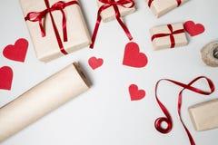Voorbereiding voor Valentine-dag met giftdozen, rood lint en hij Stock Fotografie