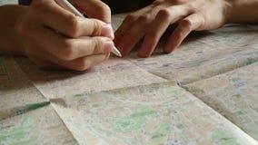 Voorbereidingen treffend te reizen, tekens een punt op de kaart overhandigen stock videobeelden