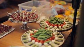 Voorbereidingen treffend voor catering, groenten en desserts op dienbladen stock video
