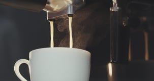 Voorbereidingen treffende en dienende verse koffie bij een upmarket cafetaria De gietende espresso van de koffiemachine in kop stock video