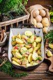 Voorbereidingen voor bakselaardappels met rozemarijn Stock Afbeeldingen