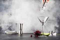 Voorbereidings Klassieke alcoholische cocktail cosmpolitan met wodka, likeur, Amerikaanse veenbessap, kalk, ijs en oranje schil,  royalty-vrije stock afbeelding
