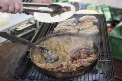 Voorbereidingsworsten met gestoofde kool op een grill Royalty-vrije Stock Foto's