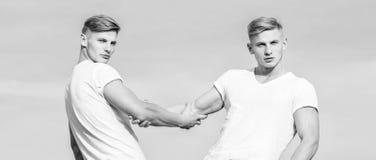 Voordelen om tweelingbroer te hebben Vriendschap en steun Broers van mensen de spiertweelingen op de witte achtergrond van de ove stock fotografie