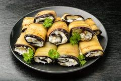 Voorgerecht - auberginebroodjes met roomkaas, knoflook dat en greens worden gevuld stock foto