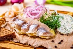 Voorgerecht De haringen, gekookte aardappel, roosterden brood, groenten in het zuur, ui op houten raad royalty-vrije stock fotografie