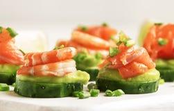 Voorgerecht met komkommer, avocado, zoute forel en garnalen op witte keuken tabe achtergrond, feestelijk snacksconcept, selectiev stock fotografie