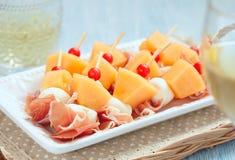 Voorgerecht met meloen, kaas en ham stock afbeeldingen