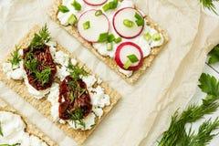 Voorgerecht van geitkaas op papier op een witte houten achtergrond Kwark, radijs, kaas, in de zon gedroogde tomaten en greens stock afbeelding