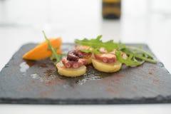 Voorgerecht van octopus met aardappels en arugula op zwarte plaat Stock Afbeeldingen
