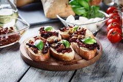 Voorgerechtbruschetta met in de zon gedroogde tomaten, olijven en mozarella Stock Afbeeldingen