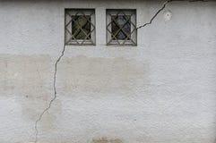 Voorgevel met 2 kleine, versperde vensters waareen lange en brede barst van ongeveer 3 meters in het metselwerk doorneemt stock foto's